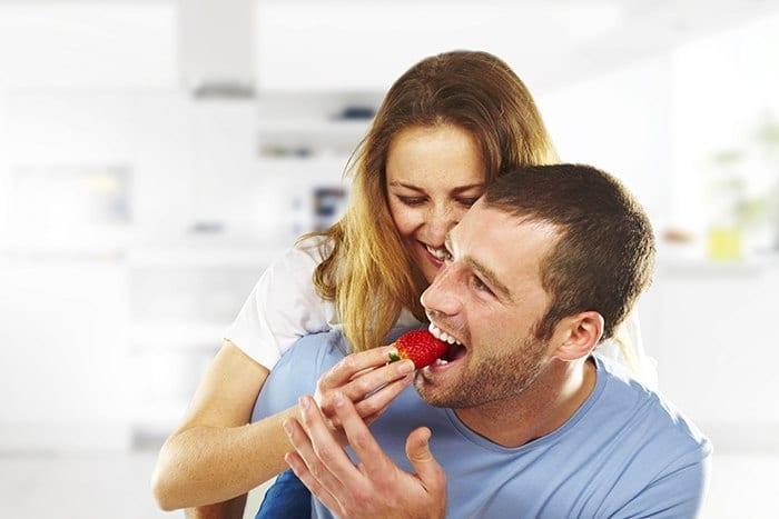 happy couple eating strawberries
