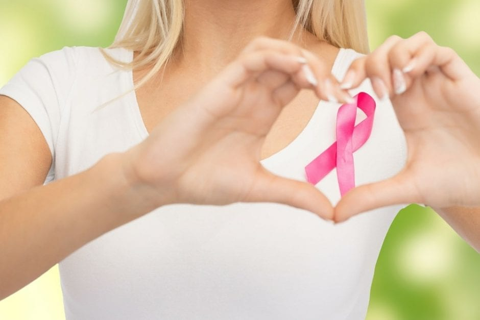 woman making the heart symbol with hands over the breast awareness ribon
