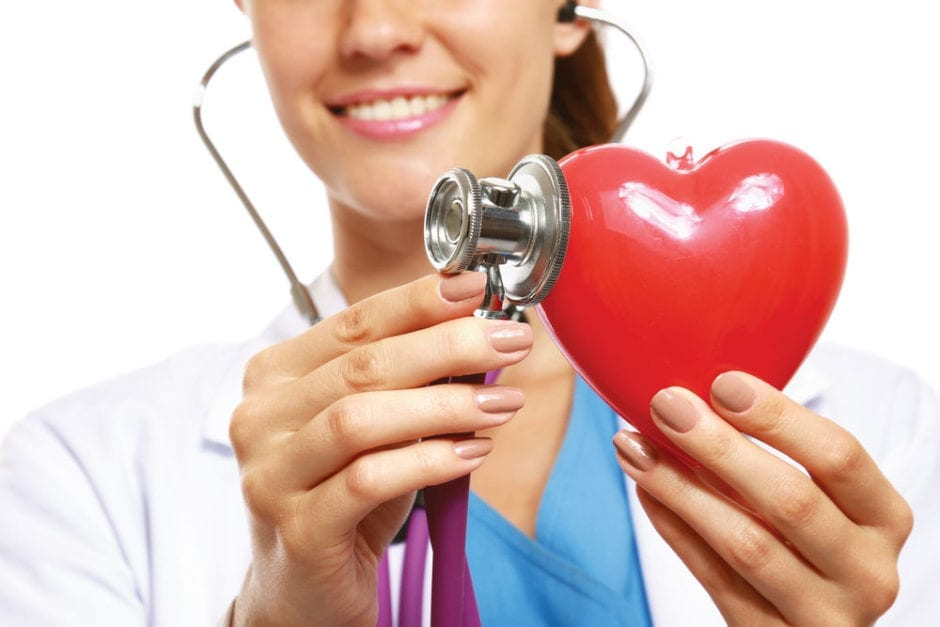 doctor with a stithoscope touching a red toy heart